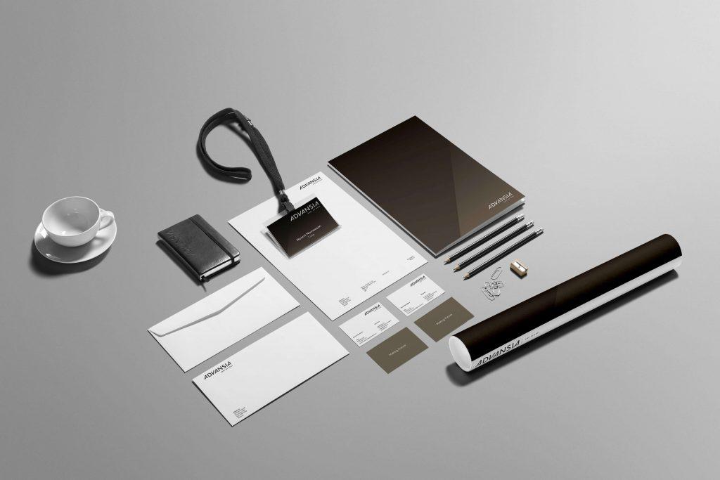 Grafisk profil for Advansia presentert på brevark, konvolutt, visittkort, papirrull, notatblokk og penner